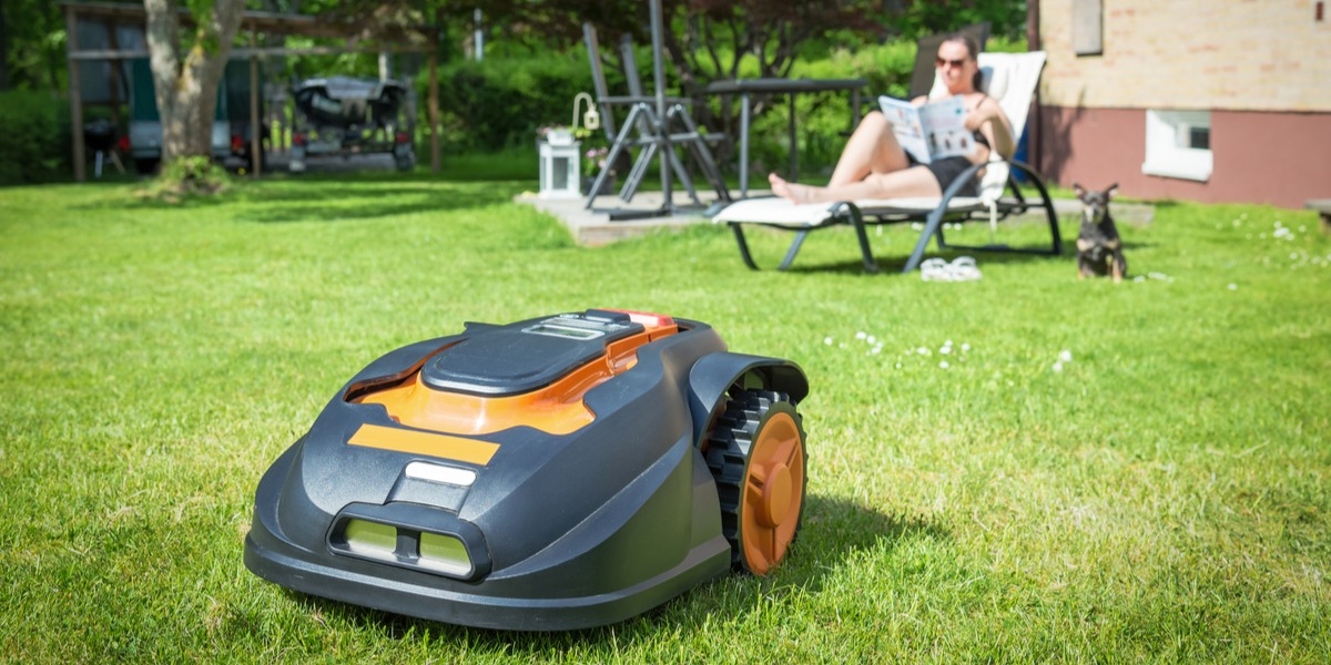 A robotic lawn mower taking care of the lawn while a woman relaxes in the back