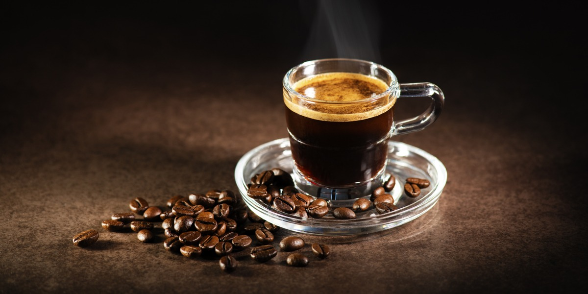 A cup of espresso and some coffee beans on a black surface