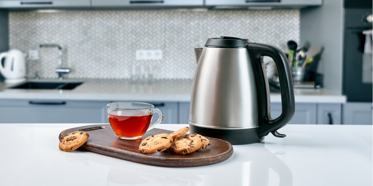An electric kettle next to a cup of tea and some cookies