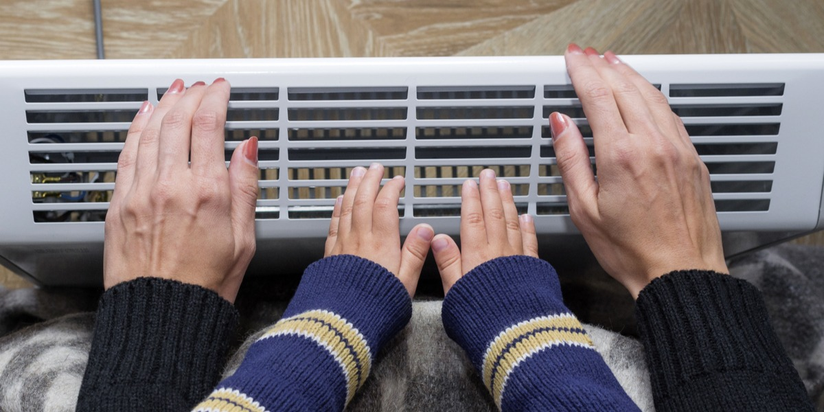 A mom with her kid warming their hands on an electric heater