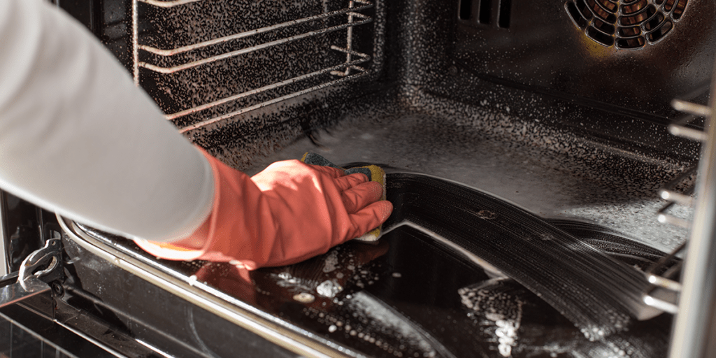 Woman cleaning the inside of an oven's door