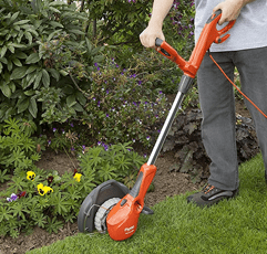 Man trimming grass with Flymo Contour 500E Electric Grass Trimmer