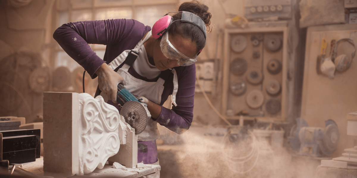 woman using angle grinder wearing eye goggles