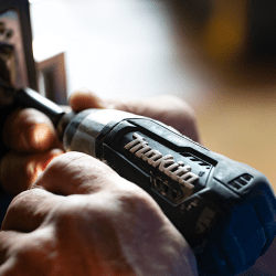 Close up to a man's hand drilling with a cordless drill