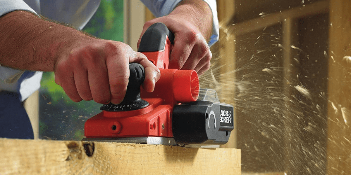 carpenter working with wood with electric planer