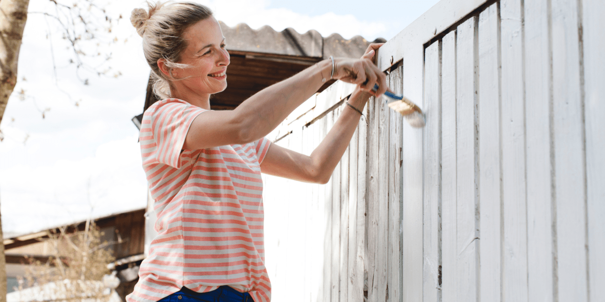 happy woman painting fence at home with the best fence paints