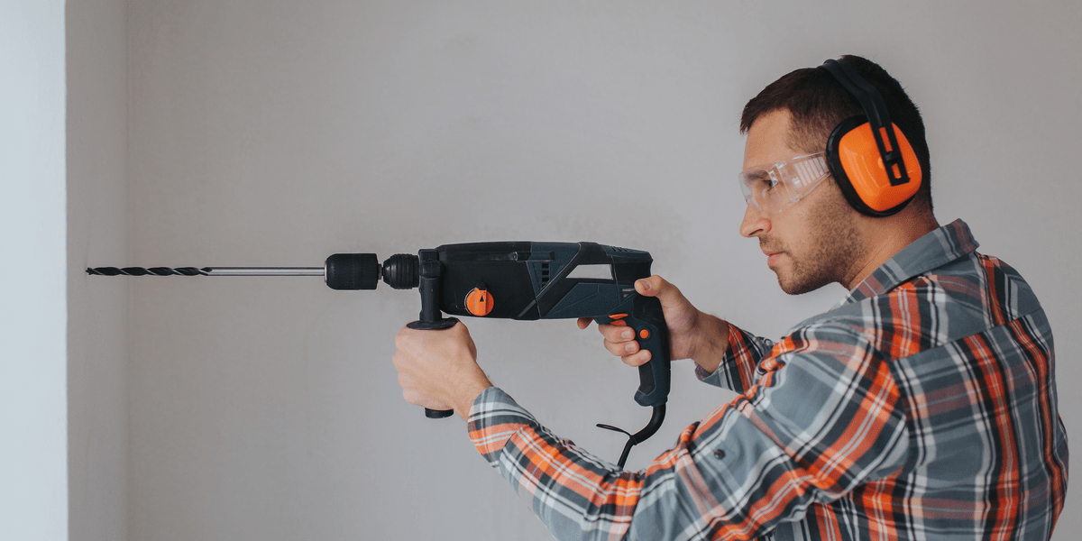 man wearing plaid shirt and protective gear on ears and eyes using hammer drill to drill wall