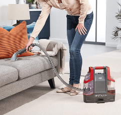 woman cleaning sofa with the Vax SpotWash Spot Cleaner