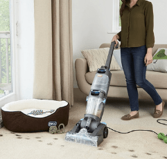 woman using Vax Dual Power Carpet Cleaner to clean dog paws off the carpet in the living room