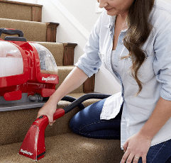 woman with Rug Doctor Portable Spot Cleaner cleaning the carpet in the stairs