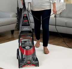 woman cleaning with BISSELL Stain Pro 6 the carpet in the livvingroom