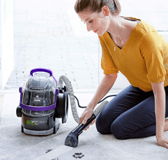 Woman cleans her carpet with BISSELL SpotClean Pet Pro carpet cleaner machine