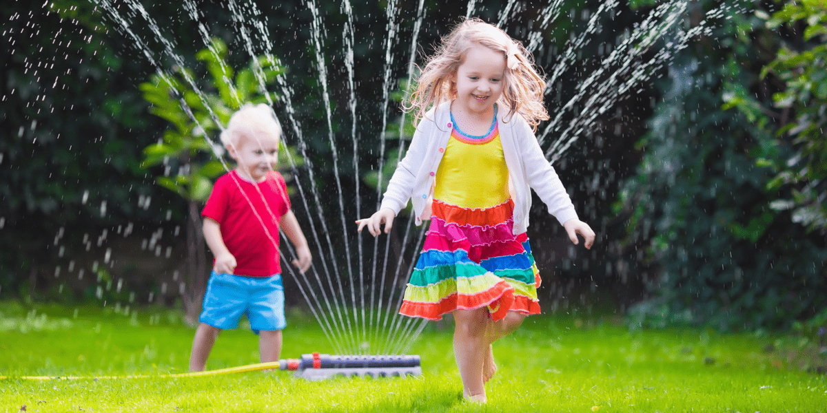 two young children smiling and playing in their backyard while the garden sprinkler is spraying water on the lawn