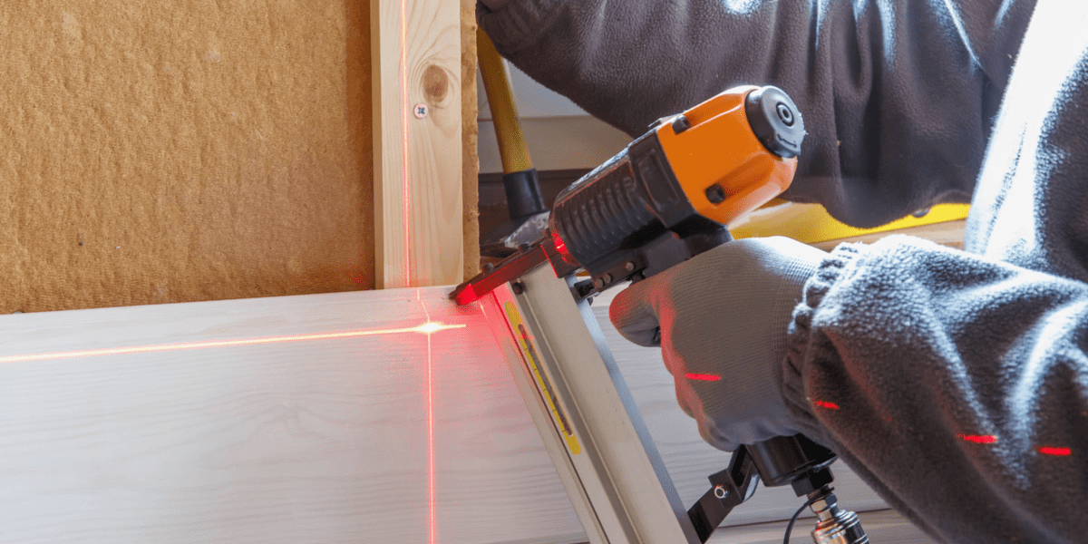 man using a laser level on wooden surface with red beam light