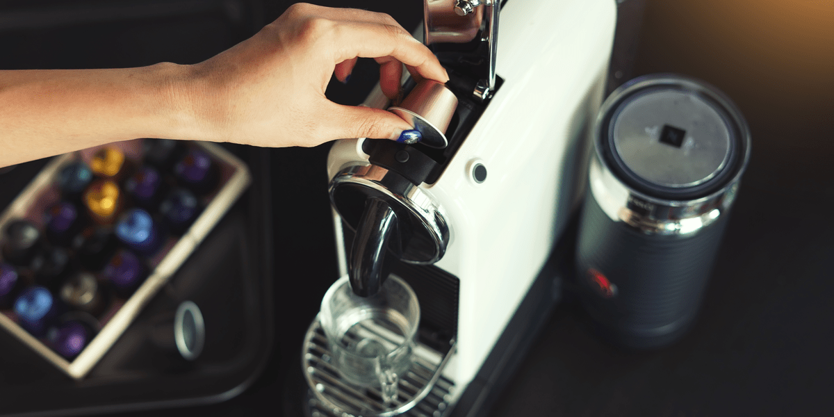 woman placing coffee pod in a stylish pod coffee machine with capsules nearby in a case