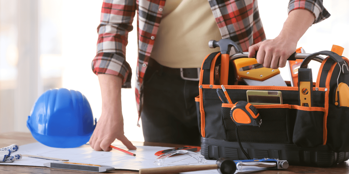 man with construction helmet carries a tool bag with all the tools needed for his DIY project