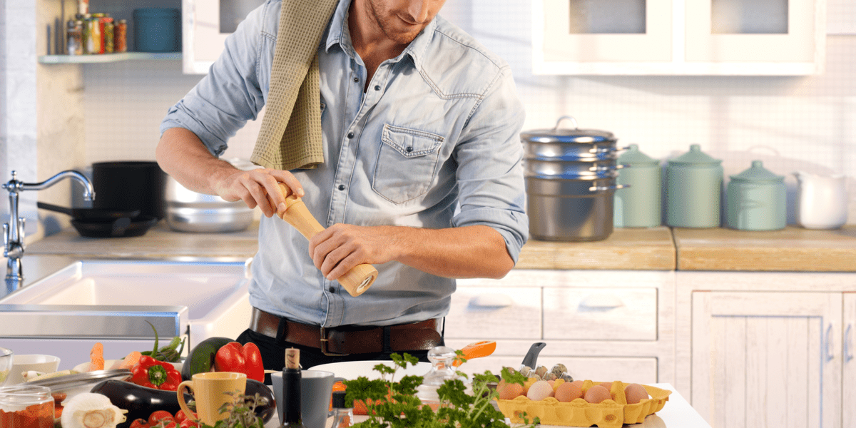 man using a wooden pepper mill in the kitchen while cooking