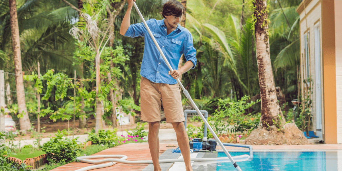man cleaning his pool with a pool cleaner