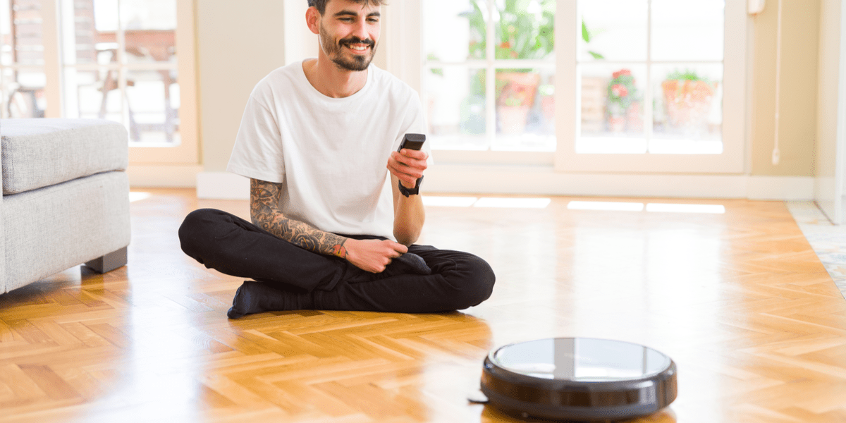 Smiling man controlling his robot mop with a remote control while it operates