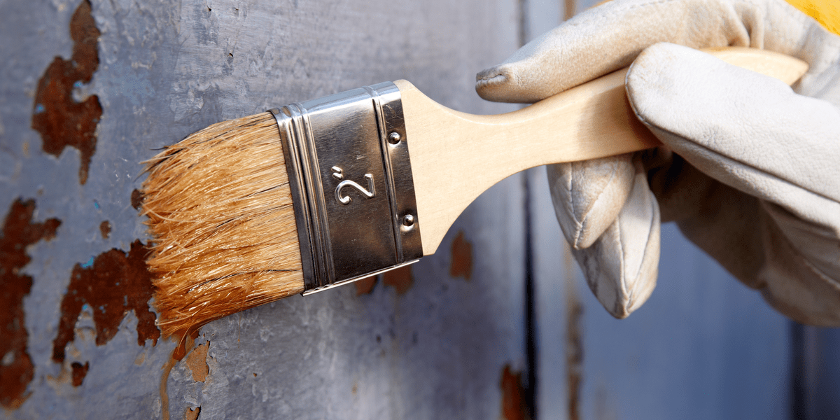 DIYer using a brush to treat rust with a rust remover