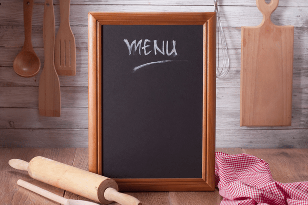 A blackboard in a wooden fram on a wooden countertop and serving spoons