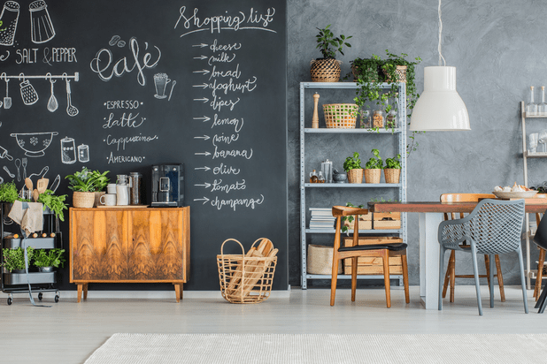 A modern kitchen and an open plan dining room with a chalkboard wall on which it's written the shopping list