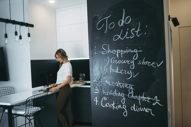 A woman is cooking in her kitchen and in the foreground a chalkboard with menu items