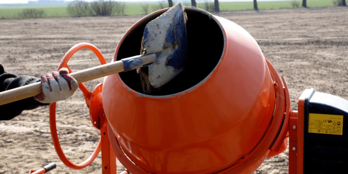 man adding cement to a cement mixer
