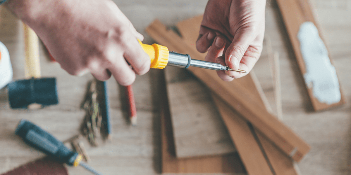 man using a screwdriver from his screwdriver set to make a furniture