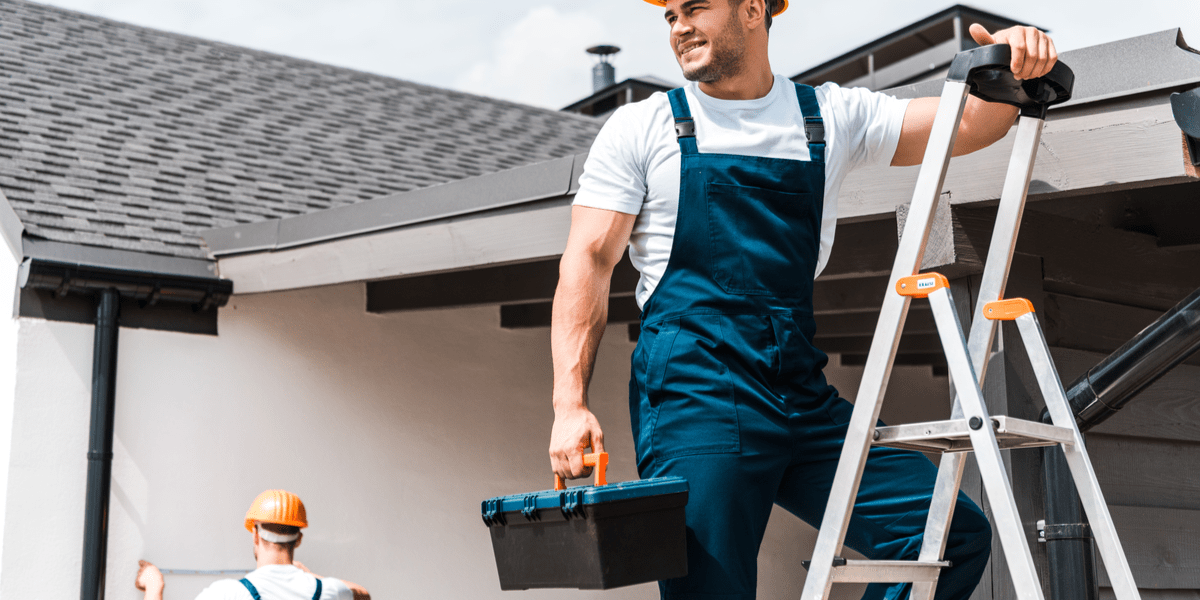 smiling male construction worker on ladder holding a toolbox