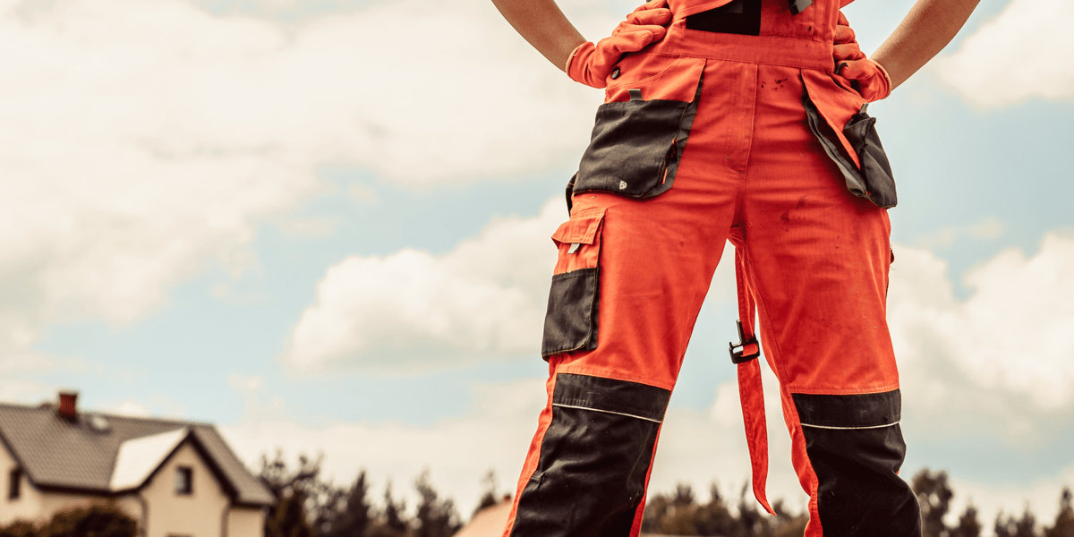 man working in construction site wearing orange work trousers with pockets