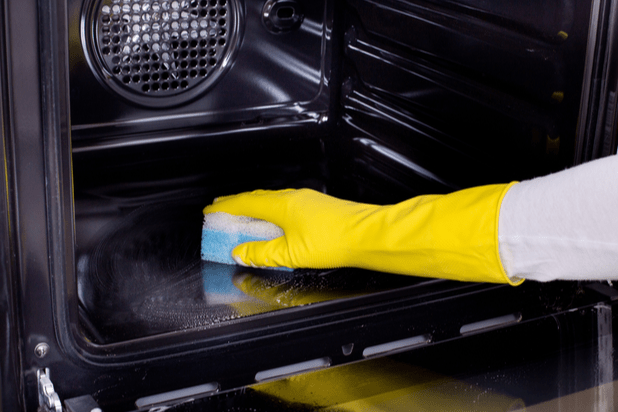 cleaning the inside of the oven wearing a cleaning glove