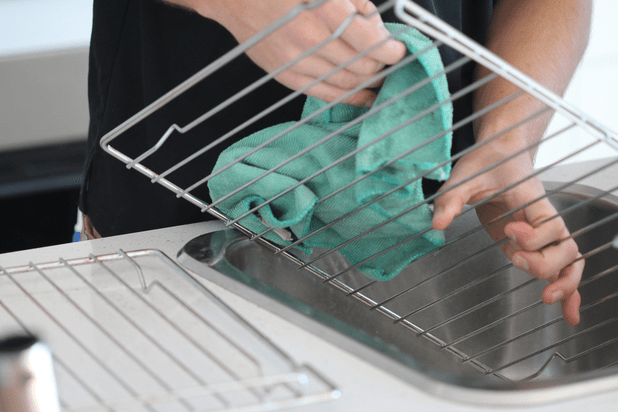 man cleaning kitchen oven rack in sink