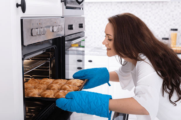 Happy young woman removing tray with baked croissants from the oven