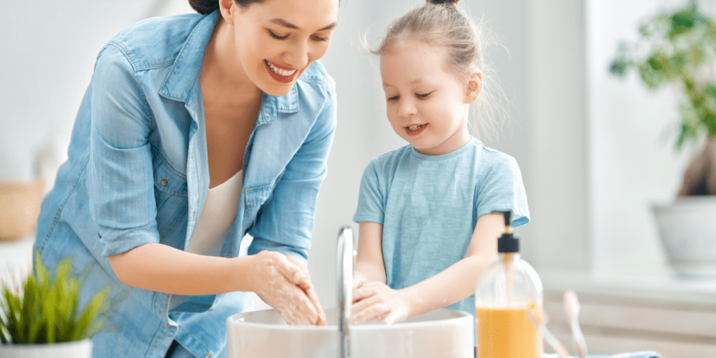 A cute little girl and her mother are washing their hands