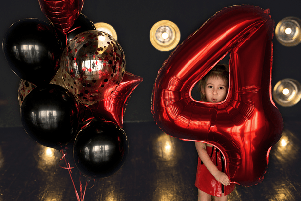 Birthday girl holding a balloon with the number four