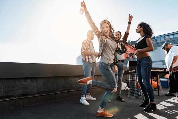 Group of friends dancing on a rooftop