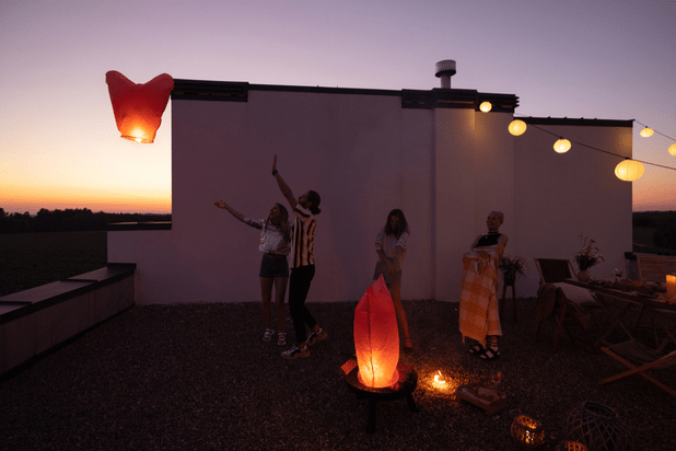Group of friends hanging out on a rooftop with paper lanterns