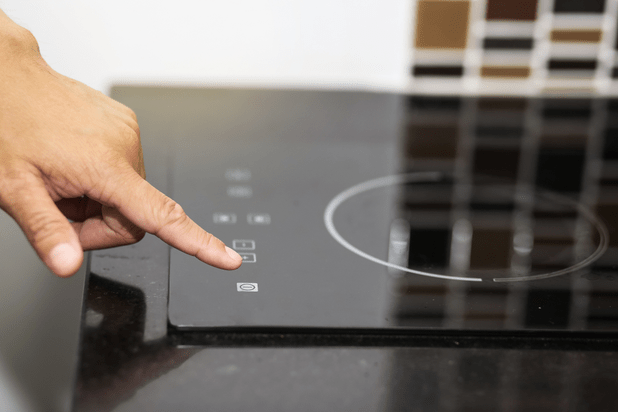 Hand switches on a modern black induction hob in a kitchen