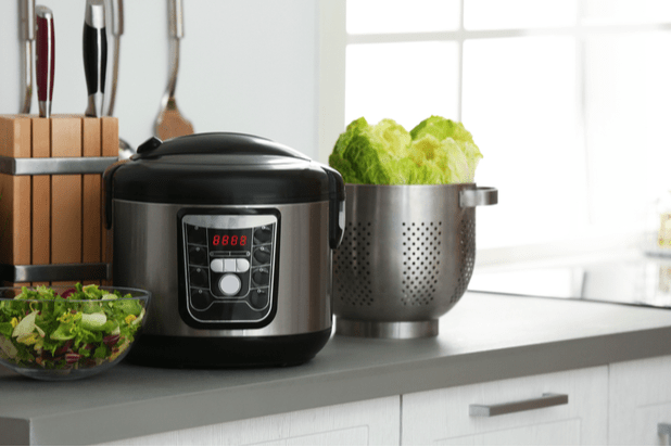 Modern electric multi cooker and food on kitchen countertop