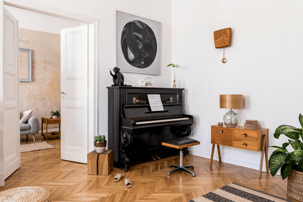 Beautiful home interior with a black piano and flowers as decor