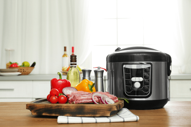 Modern multi cooker and products on wooden table