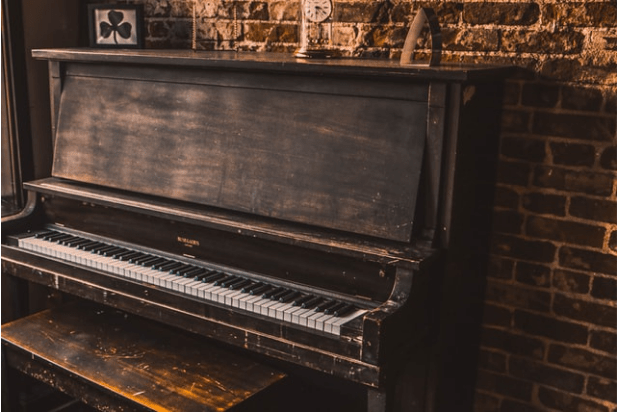 Vintage upright piano on a brick wall