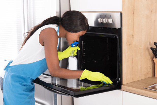 Young Woman Wearing Gloves And Cleaning The Oven With Spray Bottle And Sponge