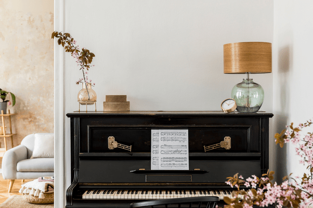modern home with a black upright piano and flowers