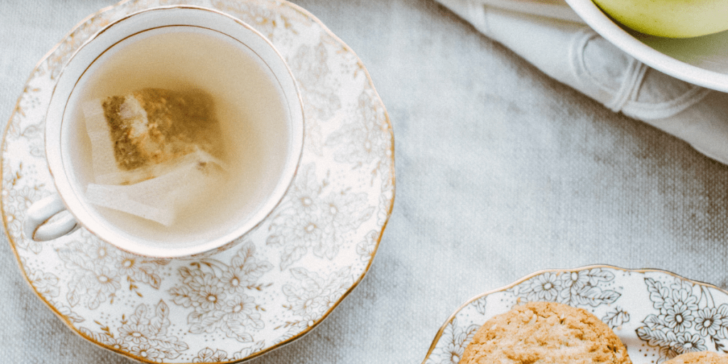 tea cup with tea bag on table with cookies and pears