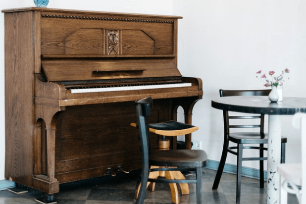 vintage upright piano on a white wall and a table with chairs
