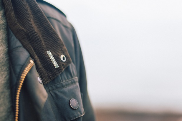 A close up of a man wearing a wax Barbour jacket