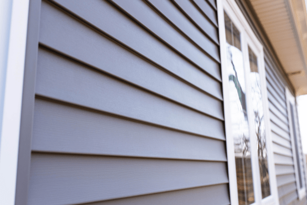 A close up of vilyl siding texture and a window