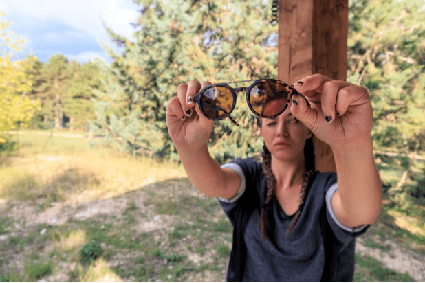 A girl is checking the sunglasses to see if the glass is dirty.